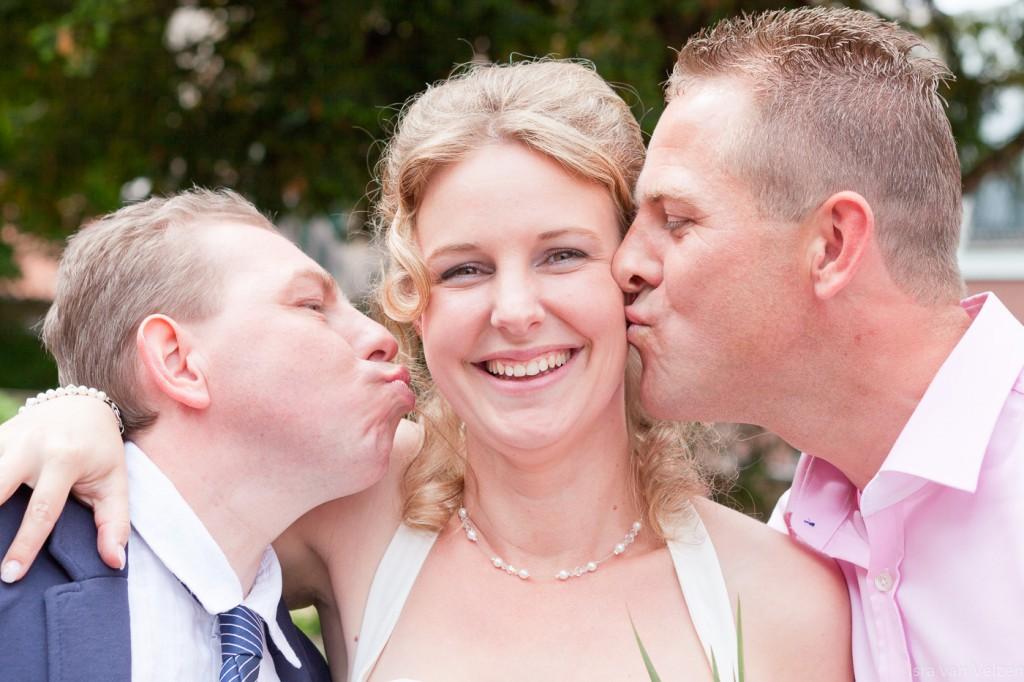 Broers zoenen bruid beide op een wang