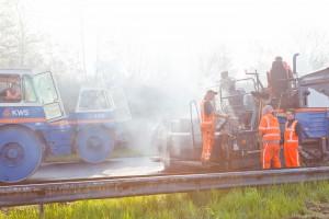 Asfalt ploeg in gesprek op asfaltmachine nabij walsen