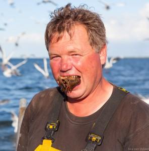 portret van visser met garnaal in zijn mond en meeuwen op de achtergrond