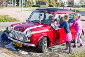 Kinderen poetsen retro Mini Cooper Cabrio huurauto