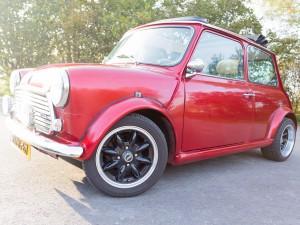 Glimmende rode retro Mini Cooper cabrio huurauto