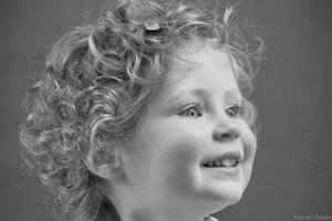 Kindje met krullen kijkt naar zijkant