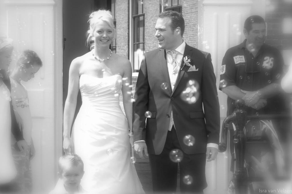Bruidspaar komt naar buiten lopen door bellenblaas