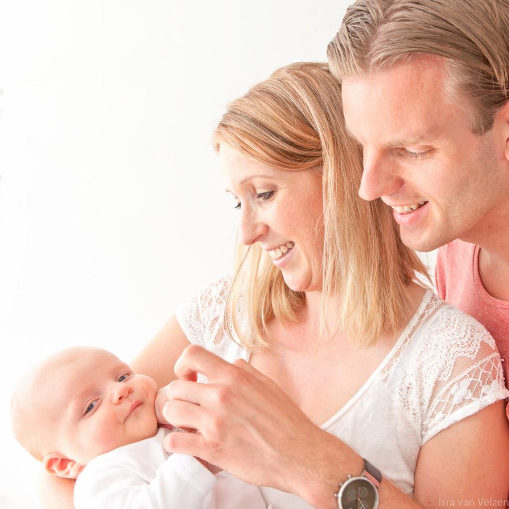 vader en moeder kijken naar baby in armen
