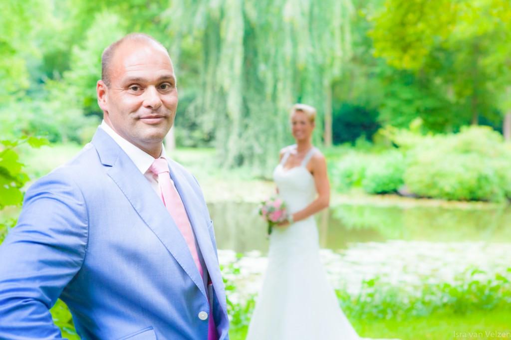 bruidegom op de voorgrond en bruid kijkt naar de bruidegom
