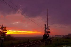 Spoorwegovergang bij zonsondergang op het platteland met spoorboom