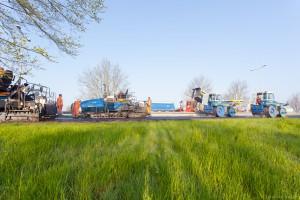 Zijaanzicht van asfaltspreiders en walsen