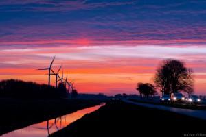 Opkomende zon Jaagweg Avenhorn met auto's en windmolens